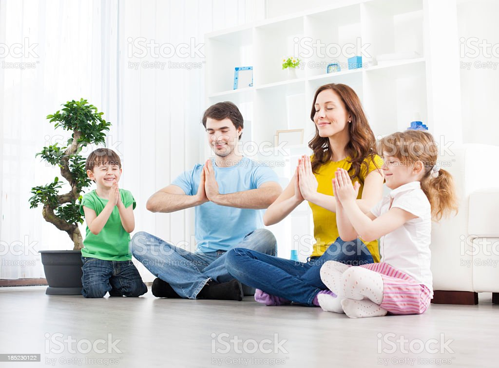 Family with children practicing yoga at home. royalty-free stock photo