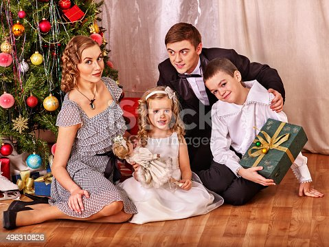 57520540 istock photo Family with children  receiving gifts under Christmas tree 496310826