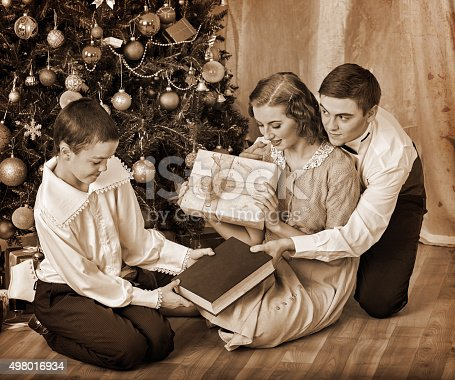 57520540 istock photo Family with children  receiving gifts under Christmas tree 498016934