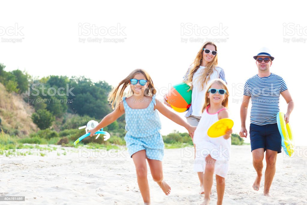 Family with children running at the beach stock photo