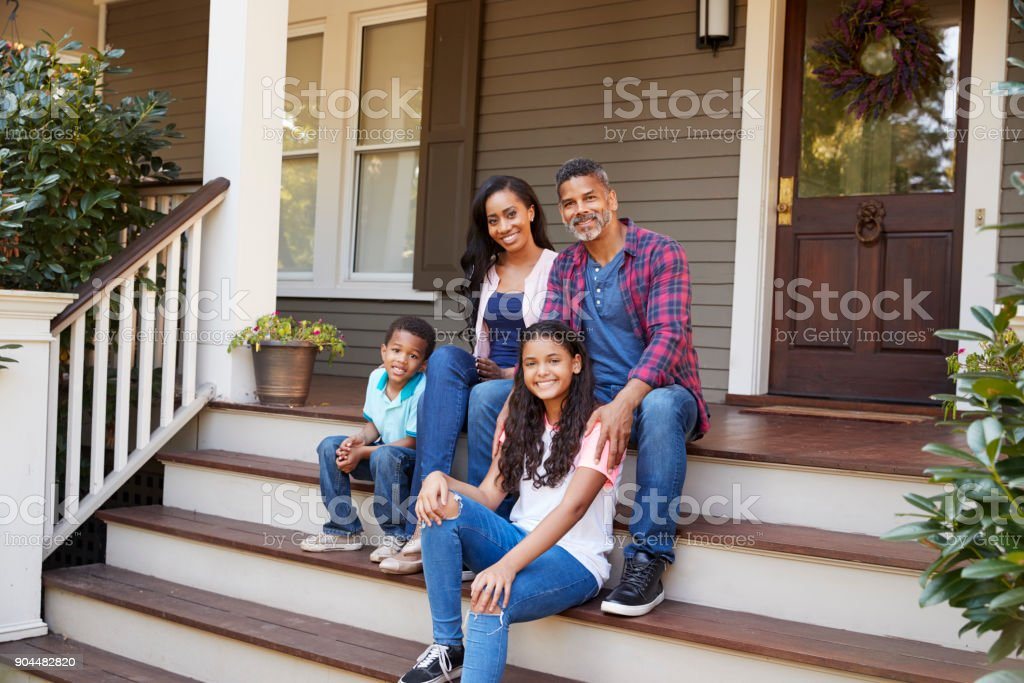 Family With Children Sit On Steps Leading Up To Porch Of Home stock photo