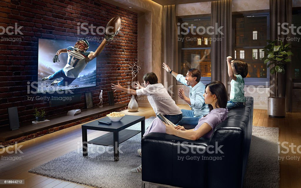Family with children watching American football game on TV - Photo