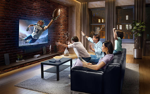 family with children watching american football game on tv - family watching tv stock photos and pictures