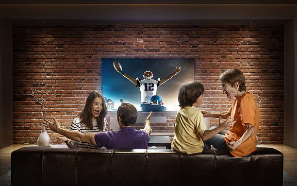 family with children watching american football game on tv - family watching tv fotografías e imágenes de stock