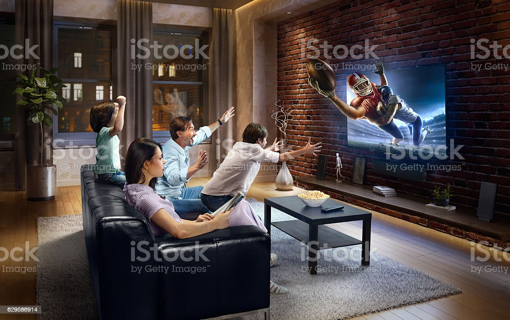 Family with children watching American football game on TV stock photo
