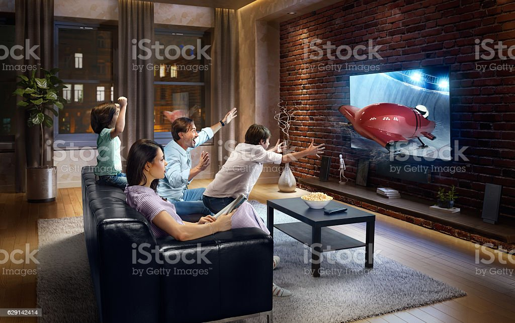Family with children watching Bobsleigh competition on TV stock photo
