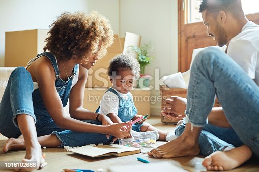 istock Family with colored pencils in new house 1016102686