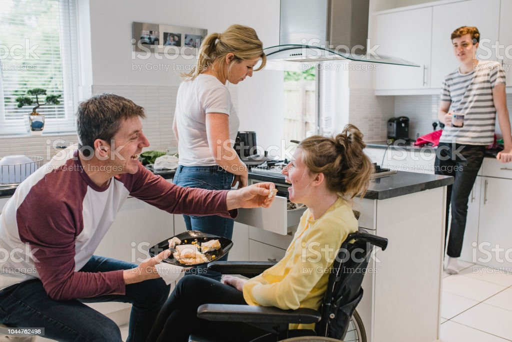 Family with Disabled Daughter in Kitchen at Home stock photo