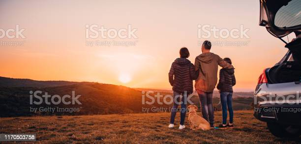 Photo of Family with dog embracing at hill and looking at sunset