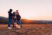 Family with dog embracing while standing on the hill during sunset