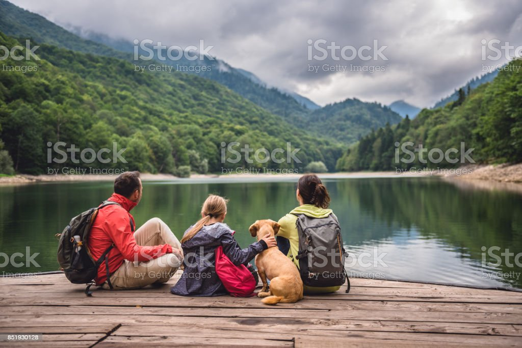 Family with dog resting on a pier stock photo