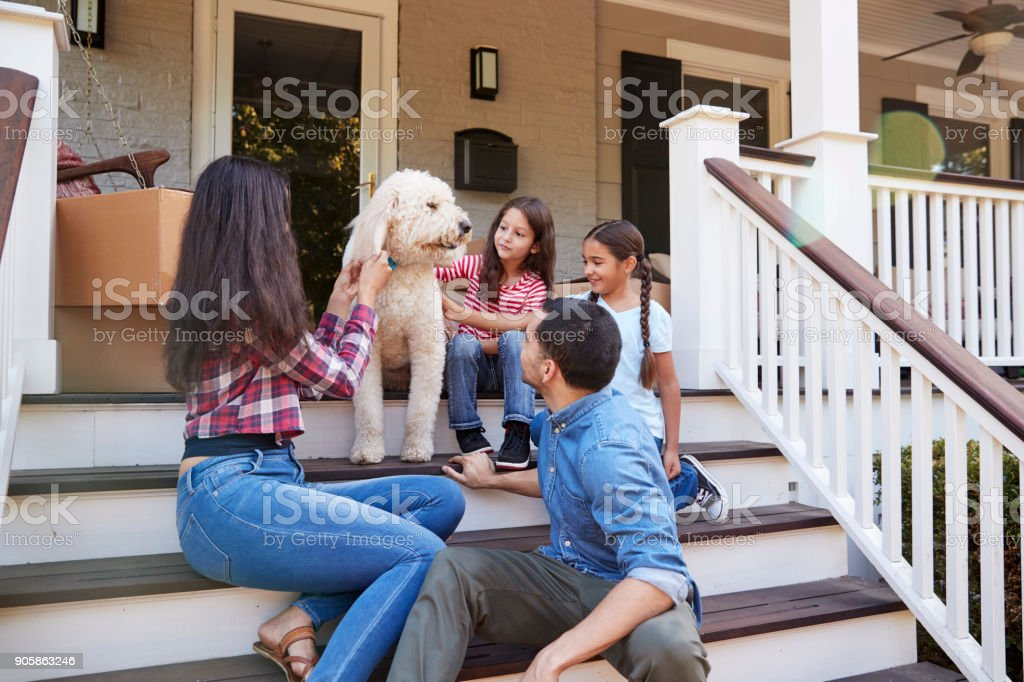 Family With Dog Sitting On Steps Of New Home On Moving In Day stock photo