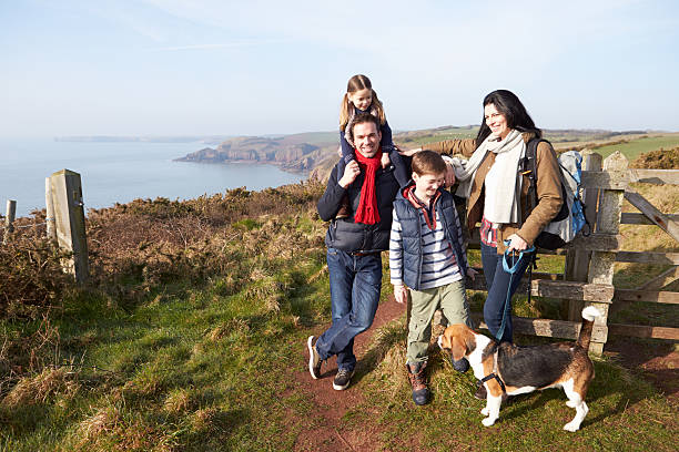 Family With Dog Walking Along Coastal Path Stock Photo