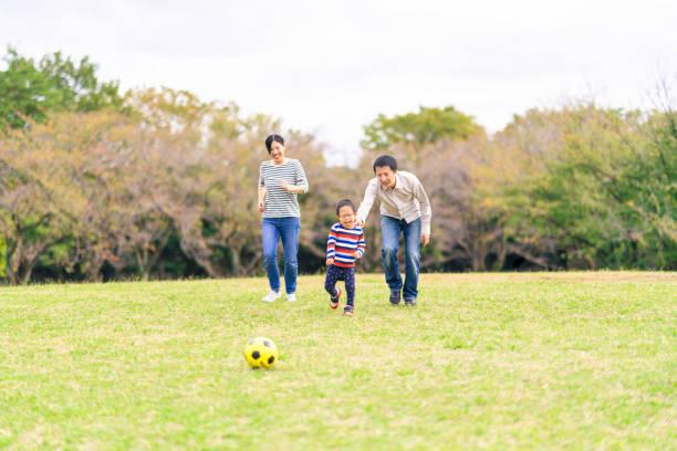 公共の公園でサッカーをしているダウン症の少年を持つ家族 - disabilitycollection ストックフォトと画像