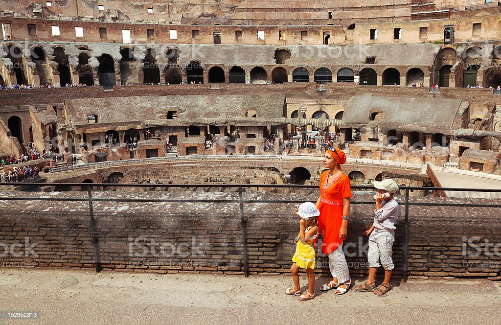 Family with electronic guide standing in arena, Coliseum royalty-free stock photo