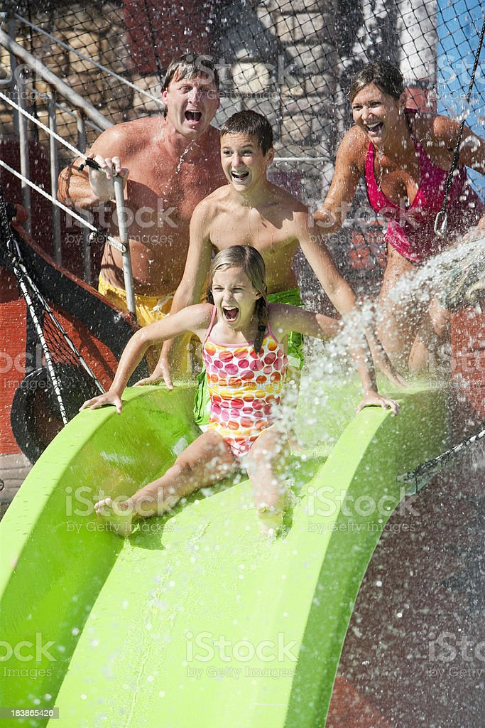 Family with girl going down slide at water park royalty-free stock photo