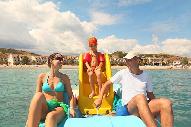 Familia con niña en bote de pedales en el mar - foto de stock