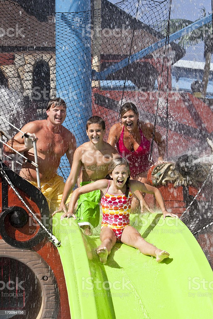 Family with girl on slide at water park royalty-free stock photo