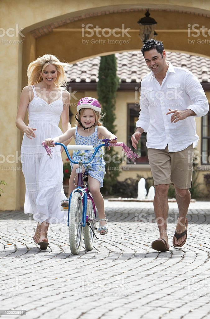 Family WIth Girl Riding Bike & Happy Parents royalty-free stock photo
