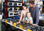 istock family with girl shopping gas-cooker in shop of household applia 628612590