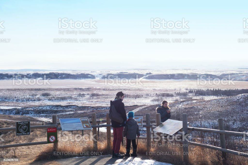 Family with grandfather,grandson and granddaughter standing near the information panel at a beautiful viewpoint in the Glenbow Ranch Provincial Park, located in the Bow Valley between the city of Calgary and the town of Cohrane , Alberta,Canada stock photo