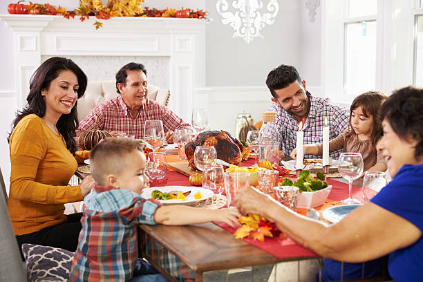 family with grandparents enjoying thanksgiving meal at table - family dinner stock photos and pictures