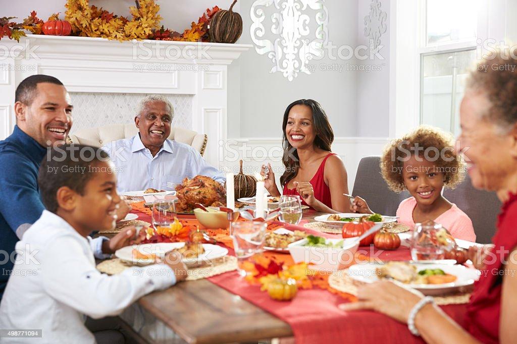 Familia con abuelos disfruta de una comida en la mesa del Día de Acción de gracias - foto de stock