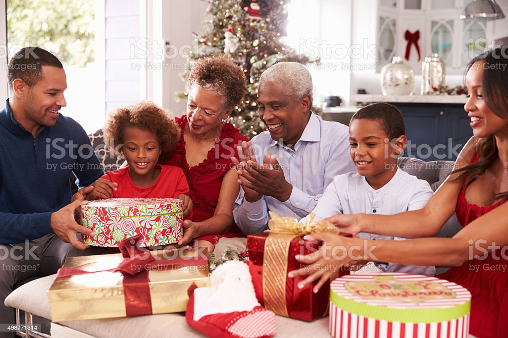 Family With Grandparents Opening Christmas Gifts stock photo