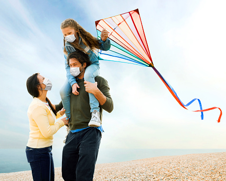 Family with daughter on father's shoulders flying kite while wearing a healthcare face mask.