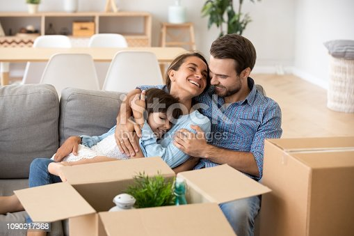 Happy mom dad with kid daughter embracing smiling relaxing on couch after relocation move in new home concept, young parents hugging child girl sitting on sofa unpacking boxes, family moving day