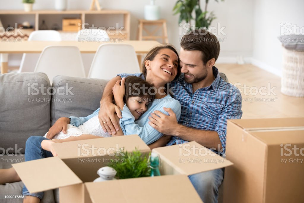 Familie mit Kind umarmen auf Sofa Umzug in neues Zuhause – Foto