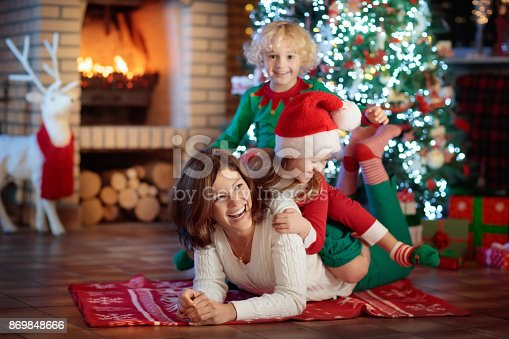 869523288 istock photo Family with kids at Christmas tree and fireplace. 869848666