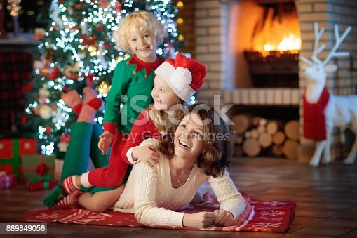 869523288 istock photo Family with kids at Christmas tree and fireplace. 869849056