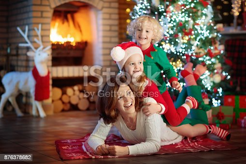 869523288 istock photo Family with kids at Christmas tree and fireplace. 876378682