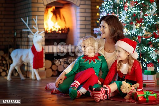 869523288 istock photo Family with kids at Christmas tree and fireplace. 876382830