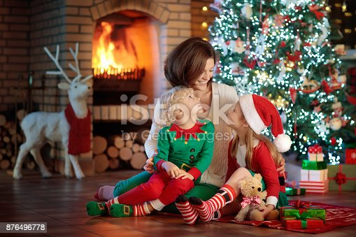 869523288 istock photo Family with kids at Christmas tree and fireplace. 876496778