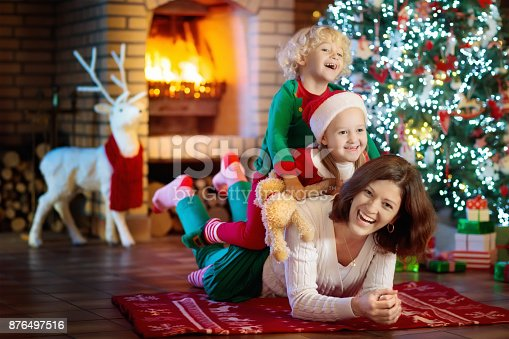 869523288 istock photo Family with kids at Christmas tree and fireplace. 876497516