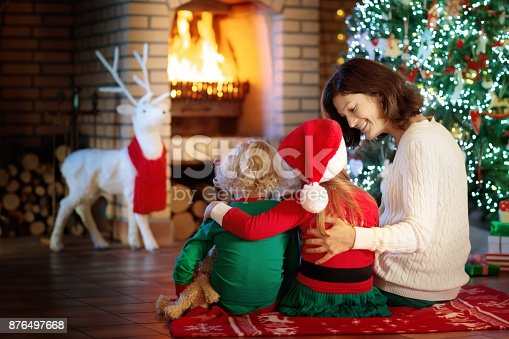 869523288 istock photo Family with kids at Christmas tree and fireplace. 876497668