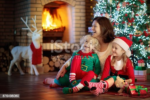 869523288 istock photo Family with kids at Christmas tree and fireplace. 876498080