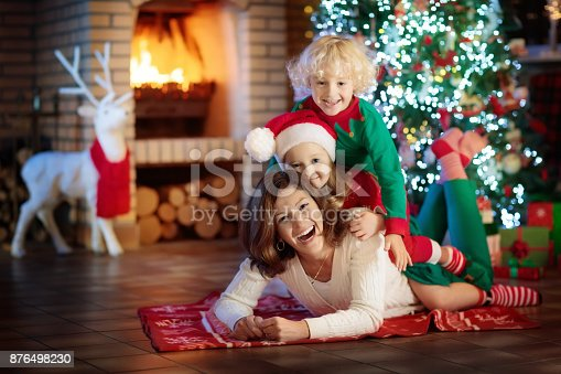869523288 istock photo Family with kids at Christmas tree and fireplace. 876498230