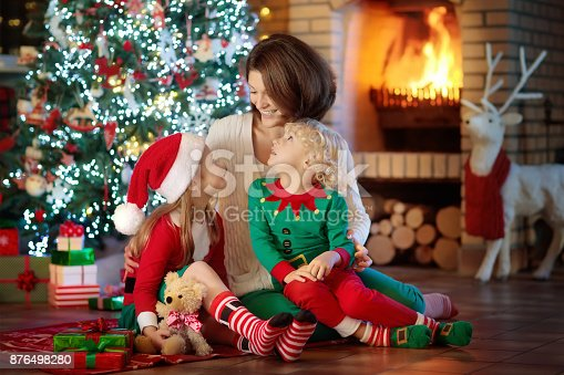 869523288 istock photo Family with kids at Christmas tree and fireplace. 876498280