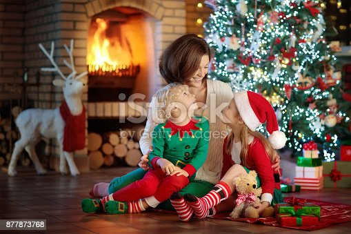 869523288 istock photo Family with kids at Christmas tree and fireplace. 877873768