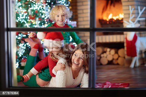 869523288 istock photo Family with kids at Christmas tree and fireplace. 877876364
