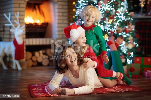 869523288 istock photo Family with kids at Christmas tree and fireplace. 877876760