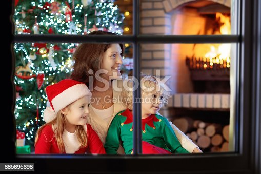 869523288 istock photo Family with kids at Christmas tree and fireplace. 885695698