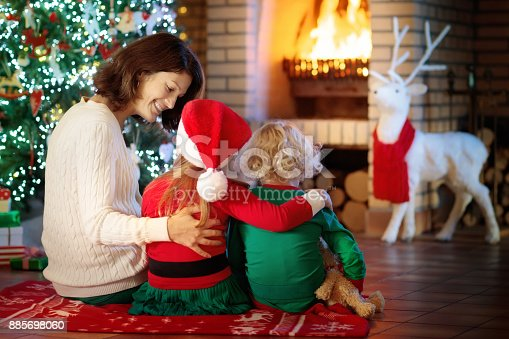 869523288 istock photo Family with kids at Christmas tree and fireplace. 885698060