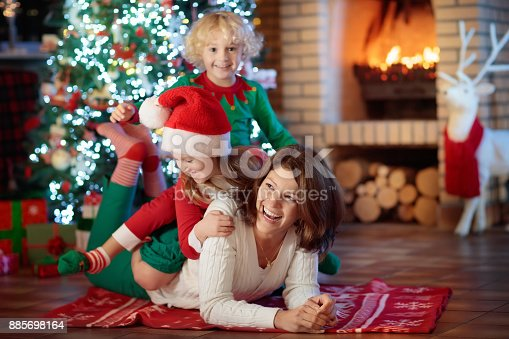 869523288 istock photo Family with kids at Christmas tree and fireplace. 885698164