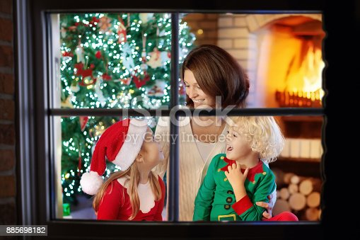 869523288 istock photo Family with kids at Christmas tree and fireplace. 885698182