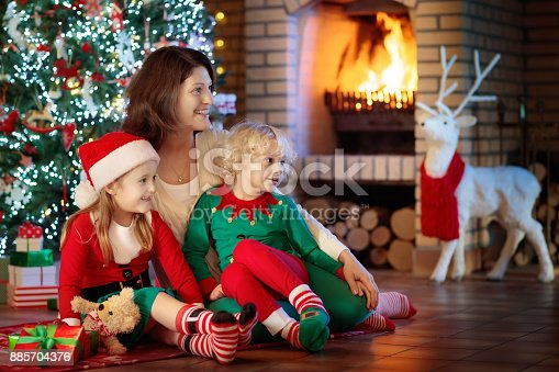 869523288 istock photo Family with kids at Christmas tree and fireplace. 885704376