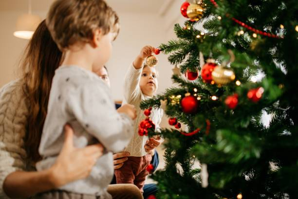 Family with kids decorating Christmas tree stock photo
